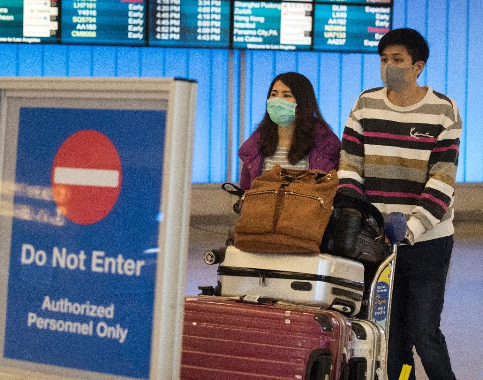 Passengers wear masks to protect against the spread of the novel coronavirus as they arrive at Los Angeles International Airport - Mark RALSTON / ©AFP
