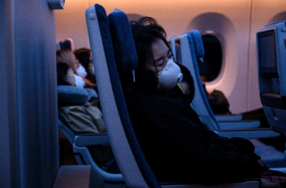 Passengers wearing protective face masks sleep on their flight to Shanghai on February 4, 2020. - NOEL CELIS / ©AFP