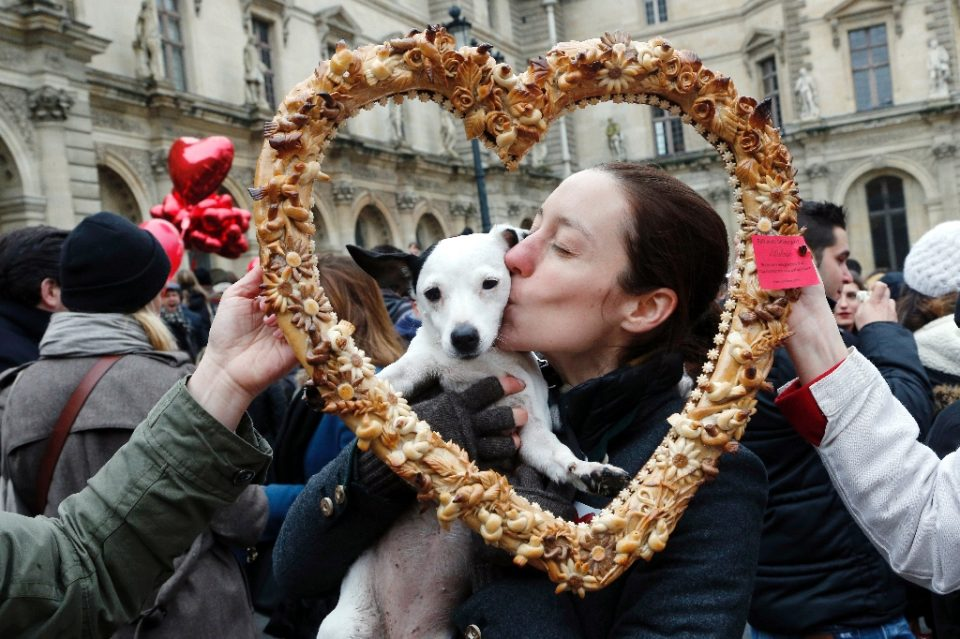 True love: a woman and her Valentine's Day date pose behind a heart-shaped pastry during a February 14 Paris flash mob (AFP)