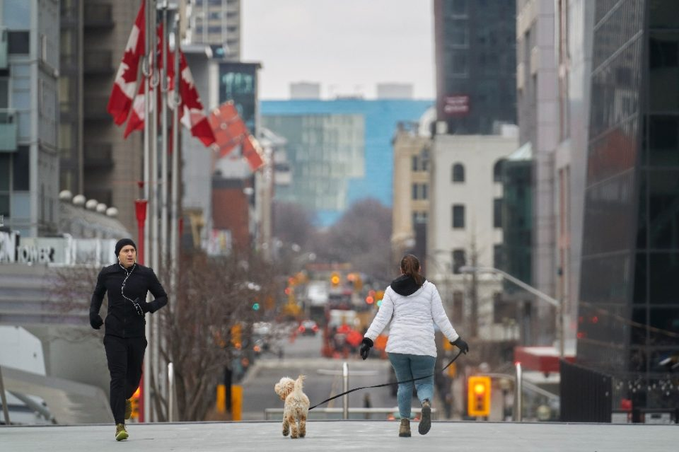 A jogger keeps his distance from a woman walking her dog in downtown Toronto, Ontario, while a Can$82 billion plan to aid Canadians cope with the economic impact of the coronavirus pandemic hit a snag in the Ottawa parliament - Geoff Robins / ©AFP