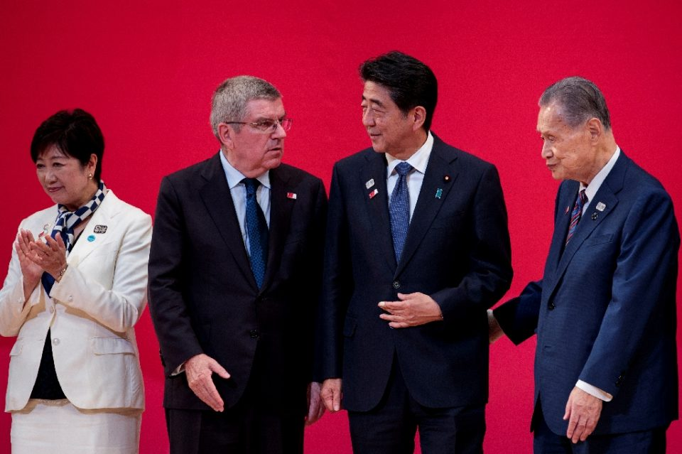 (L-R) Tokyo governor Yuriko Koike, IOC president Thomas Bach, Japanese Prime Minister Shinzo Abe and organising committee chief Yoshiro Mori have been under pressure to postpone the Tokyo Olympics - Behrouz MEHRI / ©AFP