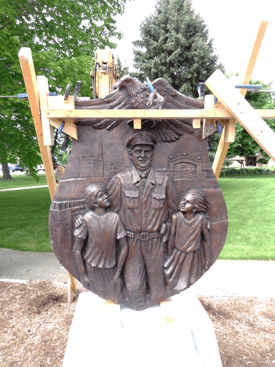 The bronze memorial of St. Clair Police Chief John D. MacDonald being moved into place in front of the senior citizen residence in St. Clair in 2015.