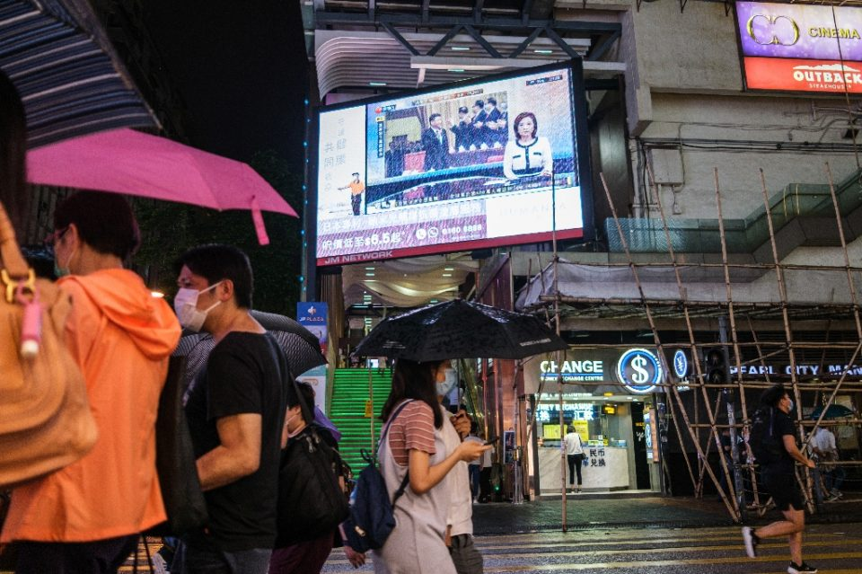 Pedestrians walk under a television screen in Hong Kong showing a news broadcast of Chinese President Xi Jinping - Anthony WALLACE / ©AFP