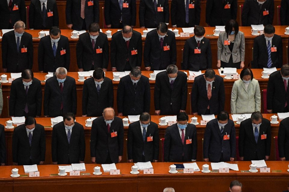 Delegates wearing face masks stand in a silent tribute for victims of the COVID-19 coronavirus during the opening session of the National People's Congress (NPC) at the Great Hall of the People in Beijing AFP / Leo RAMIREZ