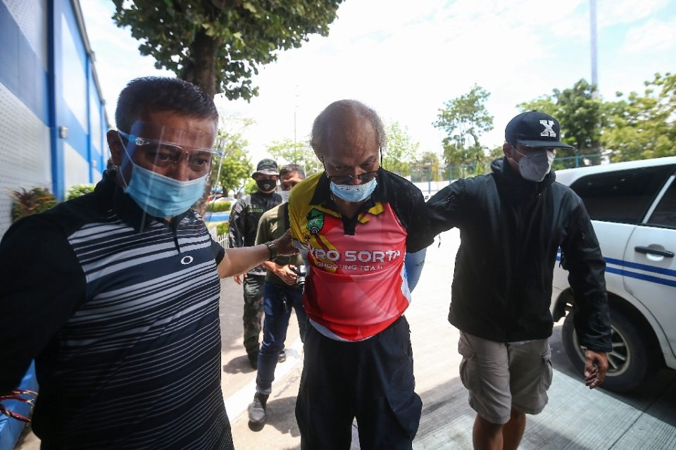 Ruben Ecleo is escorted by officers outside police regional headquarters in Manila, following his arrest (AFP Photo/STR)
