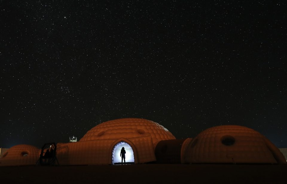 A member of the AMADEE-18 Mars simulation mission wearing a spacesuit standing in the doorway of a simulation habitat, with a view of the night sky above in Oman's Dhofar desert, in February 2018 (AFP Photo/KARIM SAHIB)