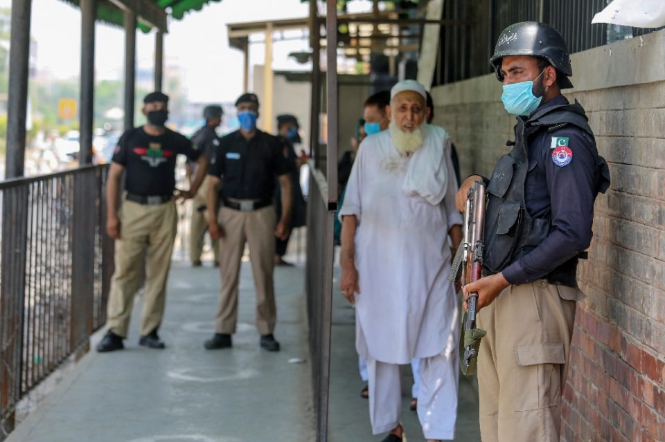 Security personnel stand guard outside a court in Peshawar, Pakistan after a man accused of blasphemy was gunned down as he started his trial on July 29, 2020 (AFP Photo/-)