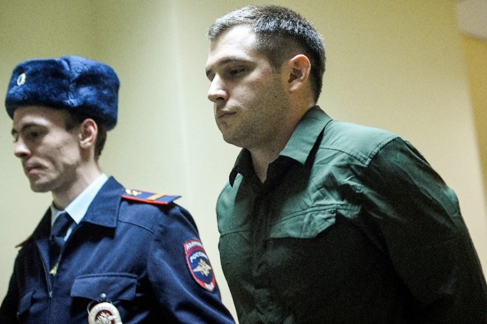 Police officers escort US ex-marine Trevor Reed, charged with attacking police, into a courtroom prior to a hearing in Moscow on March 11, 2020 (AFP Photo/Alexander NEMENOV)
