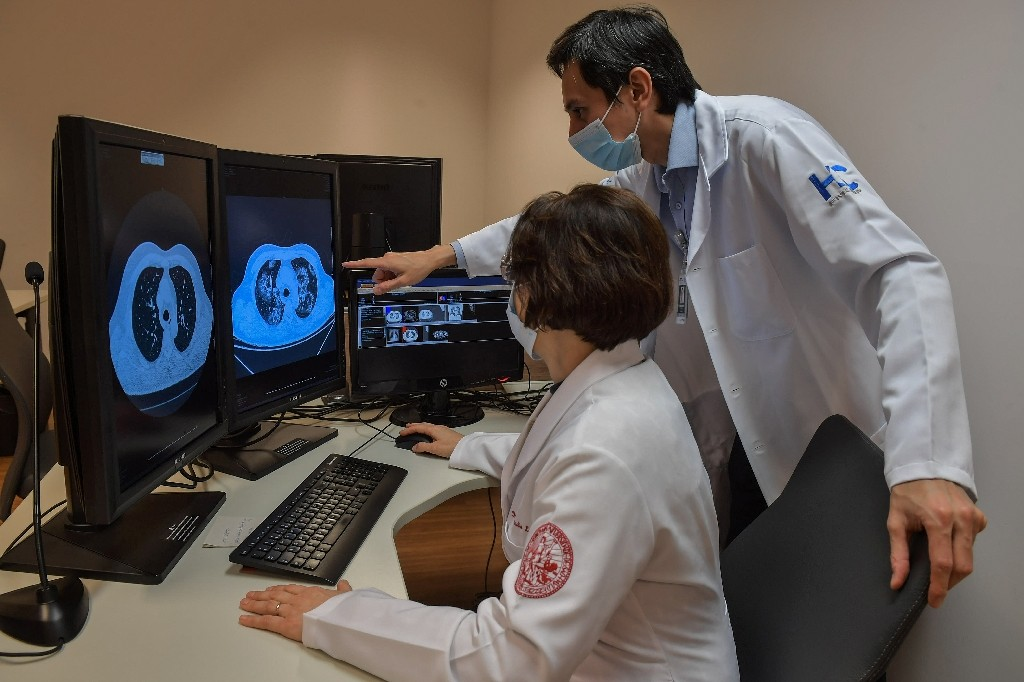 Claudia Leite (L) and Marcio Sawamura of the University of Sao Paulo Clinical Hospital look at tomography images of lungs (AFP Photo/NELSON ALMEIDA)