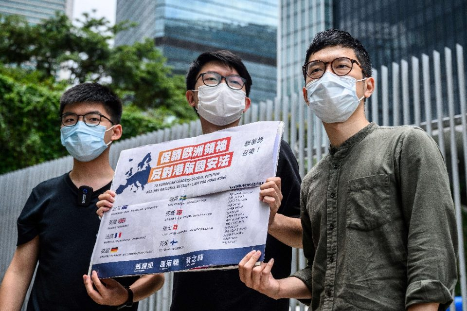Hong Kong pro-democracy campaigner Nathan Law (far right) holds a placard urging European leaders to act against a national security law in June 2020 before he fled for Britain, where Beijing says Hong Kong police are seeking his arrest (AFP Photo/Anthony WALLACE)