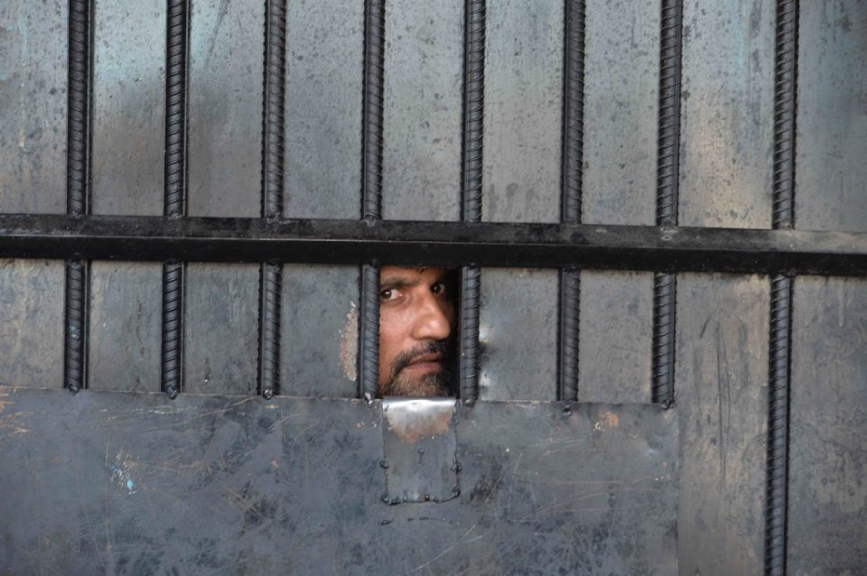 A man watches from behind a closed gate after a raid at the prison in Jalalabad (AFP Photo/NOORULLAH SHIRZADA)