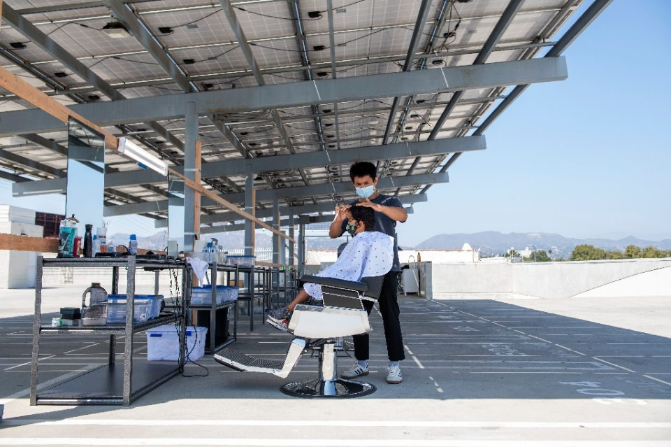 A stylist from Grey Matter LA cuts a young client's hair on a roof top parking lot in Los Angeles - VALERIE MACON / ©AFP
