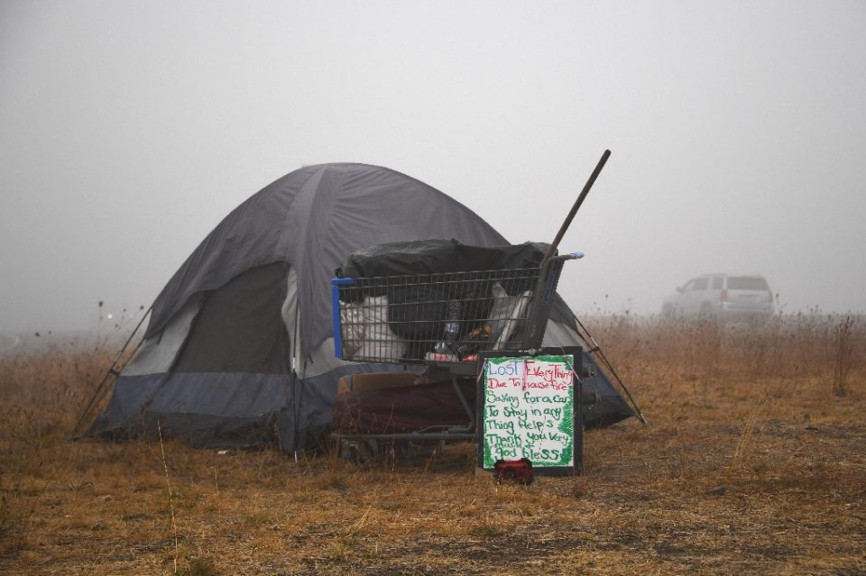 """A sign in front of a tent along the highway near Salem, Oregon on September 13, 2020 reads """"Lost Everything Due To House Fire"""" - Robyn Beck / ©AFP"""