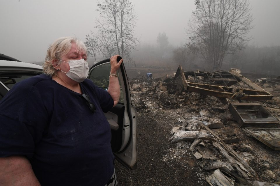 Margi Wyatt stands in front of her incinerated mobile home - Robyn Beck / ©AFP