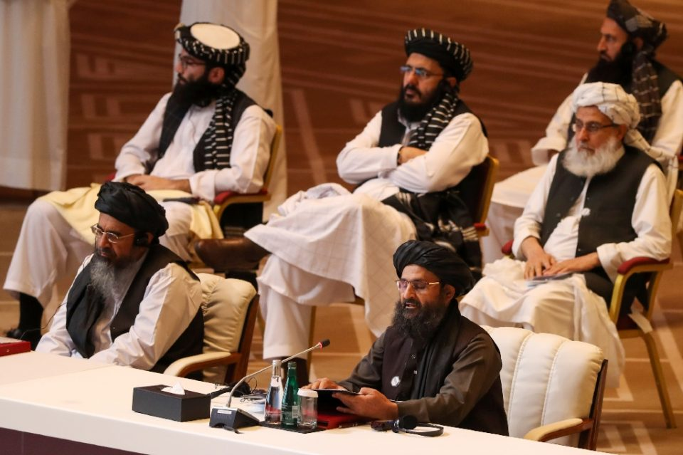 Taliban co-founder Mullah Abdul Ghani Baradar (R, bottom) speaks during the opening session of peace talks with the Afghan government - KARIM JAAFAR / ©AFP