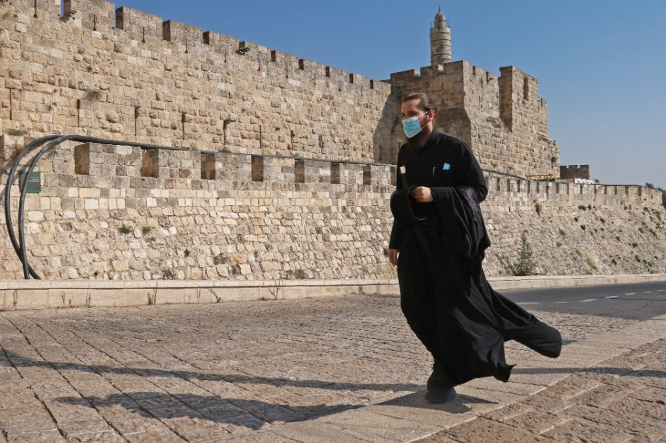 A priest, wearing a protective mask amid the Covid-19 pandemic, walks along the walls of Jerusalem's Old City on September 12, 2020 - Emmanuel DUNAND / ©AFP