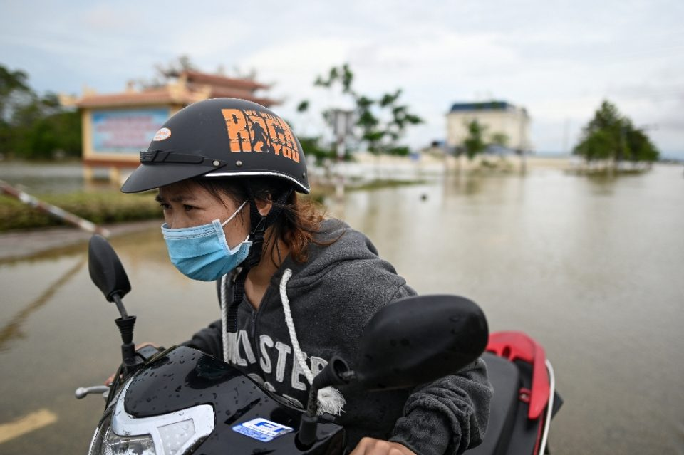 A woman pushes her scooter along a flooded road in Quang Dien district in central Vietnam's Hue province - MANAN VATSYAYANA / ©AFP