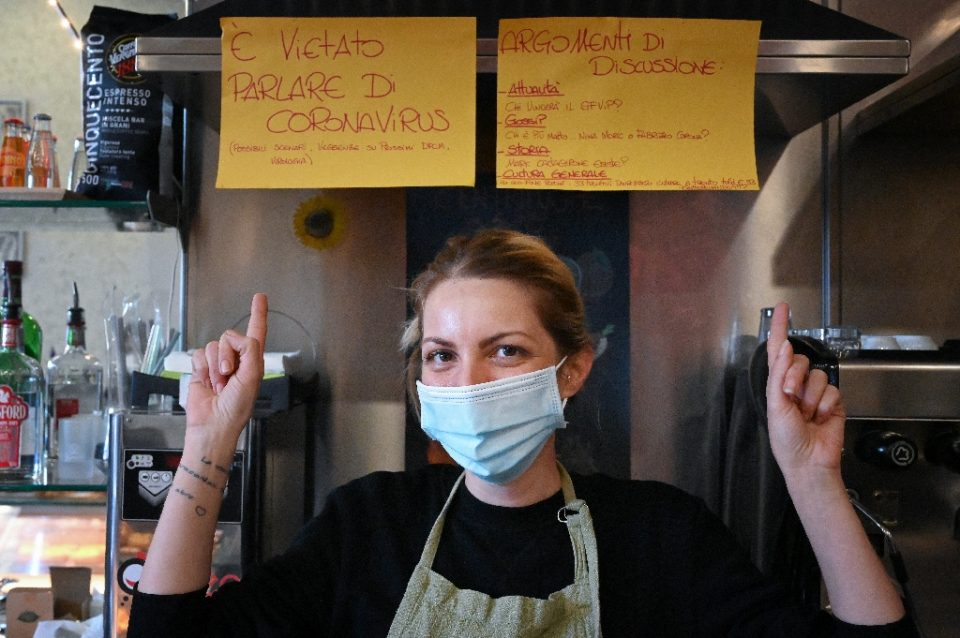 Cristina Mattioli, manager of the Feeling bar, put up one poster banning virus talk and another offering other ideas for conversation. - Alberto PIZZOLI / ©AFP