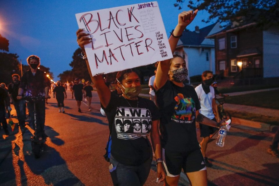A protester holds a Black Lives Matter sign during a demonstration against the shooting of Jacob Blake in Kenosha, Wisconsin on August 26, 2020, the day after Kyle Rittenhouse allegedly shot dead two protesters in the street / AFP Photo