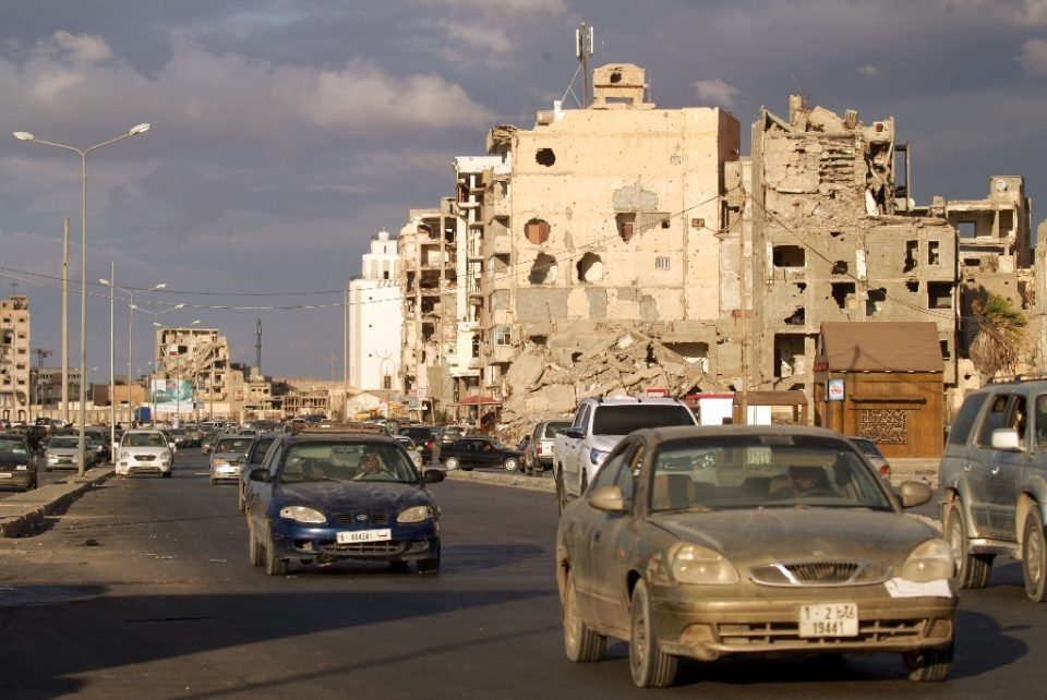 Cars drive near shell-pocked buildings in Libya's eastern coastal city of Benghazi on October 23, 2020, after a ceasefire agreement was signed between the country's warring ]]>