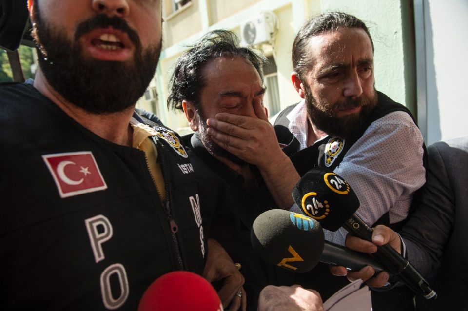 Cult leader: A Turkish police officer puts his hand over the mouth of televangelist Adnan Oktar, who was jailed Monday for 1,075 years for sexual assault - DOGAN NEWS AGENCY/AFP