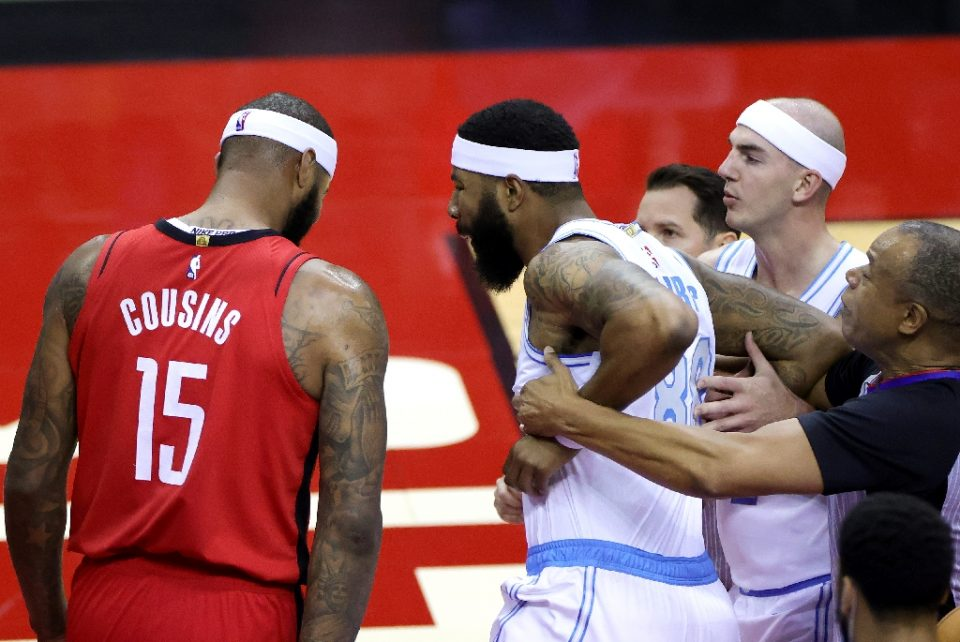 Houston Rockets center DeMarcus Cousins, left, walks away as Markieff Morris of the Los Angeles Lakers is restrained while yelling at Cousins after an on-court altercation Sunday that led to fines for each player from the NBA on Tuesday - Carmen Mandato / ©AFP