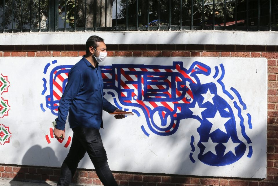 A man walks past a mural painted on the outer walls of the former US embassy in Tehran - ATTA KENARE / ©AFP