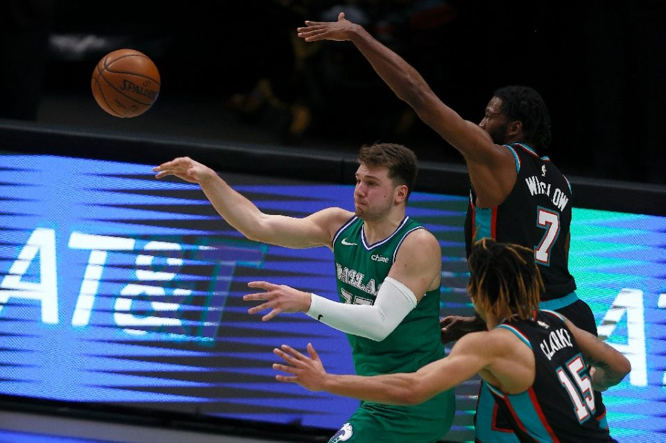 Dallas Mavericks star Luka Doncic passes the ball against Brandon Clarke, 15, and Justise Winslow ,7, of the Memphis Grizzlies in the second half at American Airlines Center - TOM PENNINGTON / ©AFP